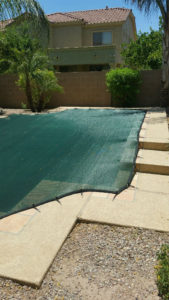 Black leaf cover covering an irregular shaped pool