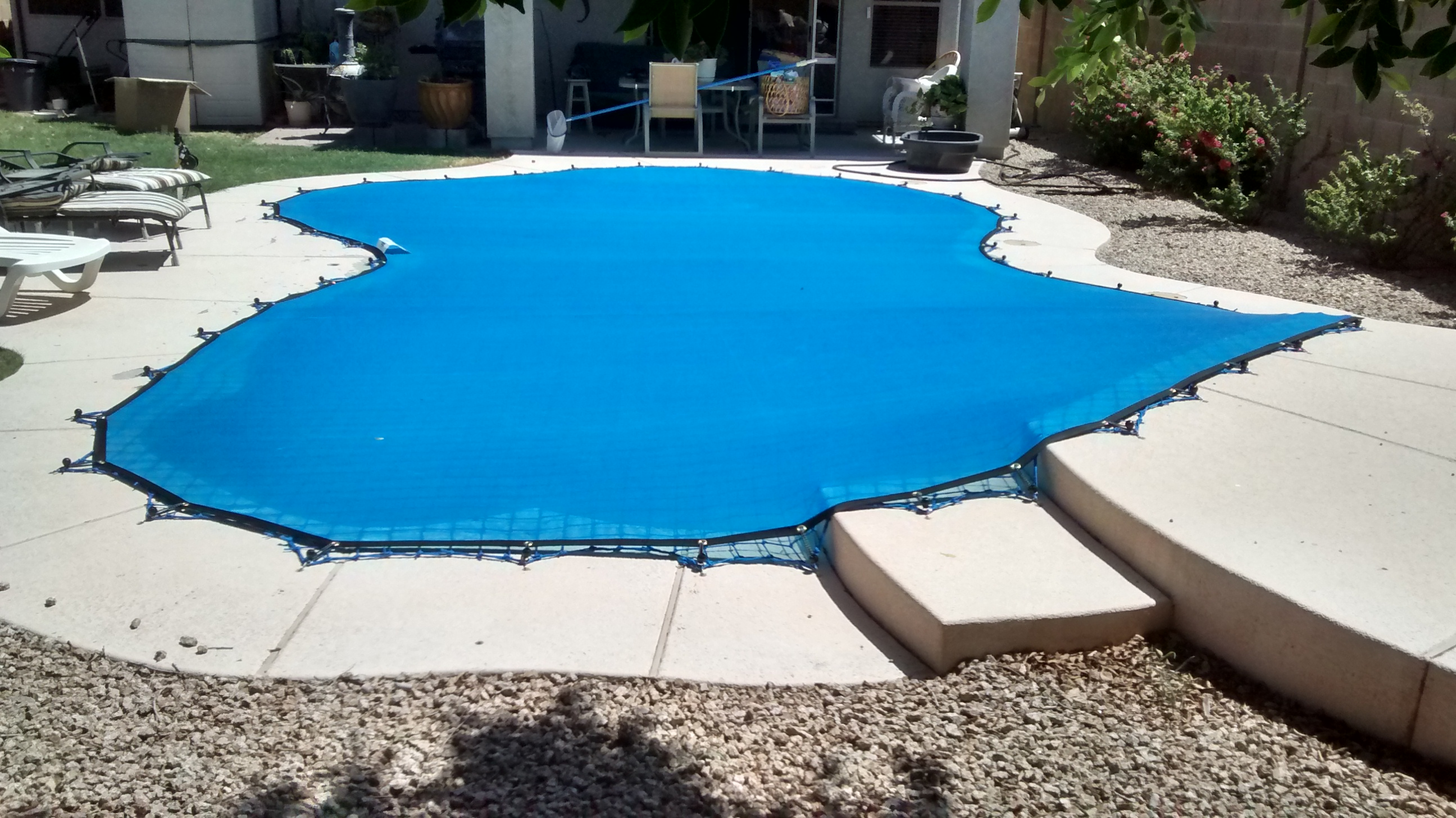 Blue pool cover with concrete pool deck