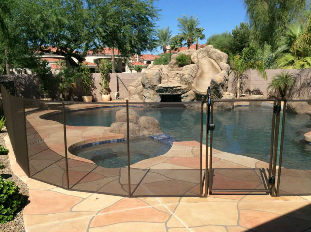 A pool safety fence prohibiting access to a pool and spa area.