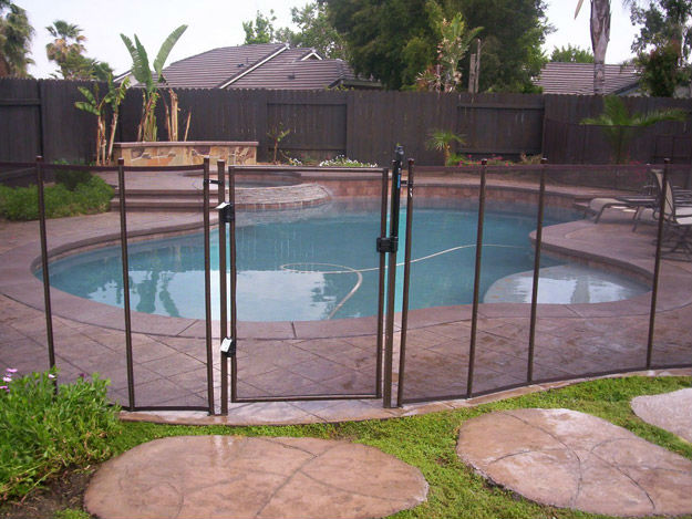 A pool safety fence installed and protecting a swimming pool.