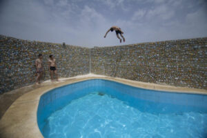 A pair of young men watch a third young man dive into a pool from a nearby wall in a dangerous stunt.