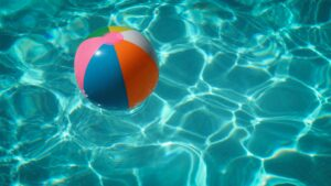 A multi-colored beach ball floating in a swimming pool.