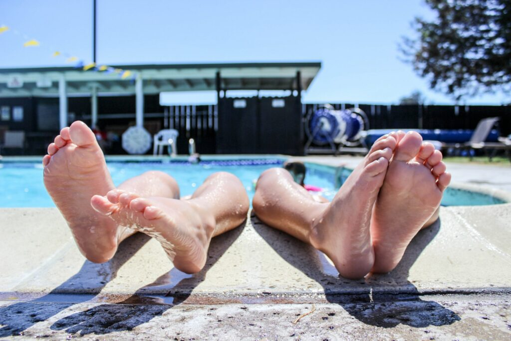 Two pairs of feat sticking out of a pool and resting on the edge.