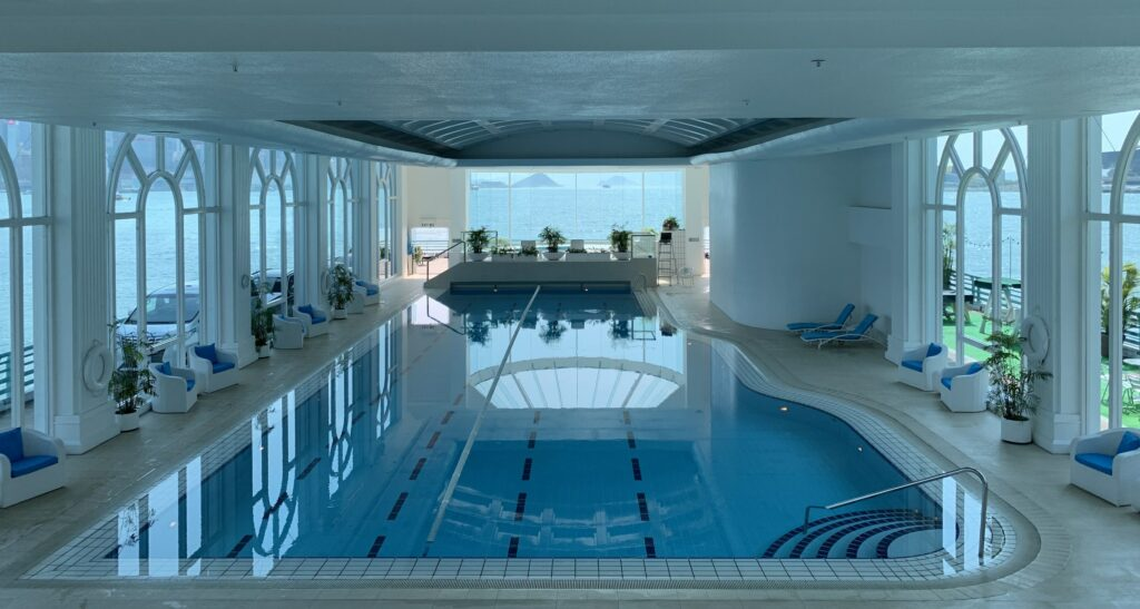An indoor swimming pool overlooking a body of water.