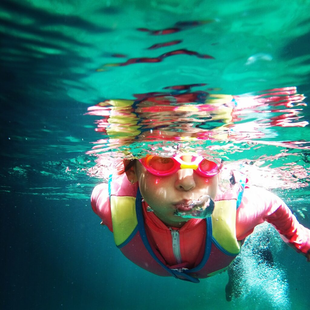 A child playing in a swimming pool with a lot of swimming gear for kids.