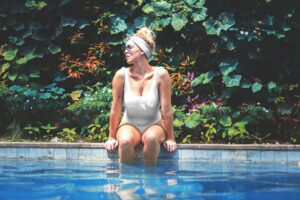 A woman sits with her legs in a swimming pool.