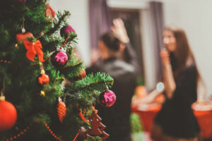 A decorated evergreen tree with a group of partygoers in the background