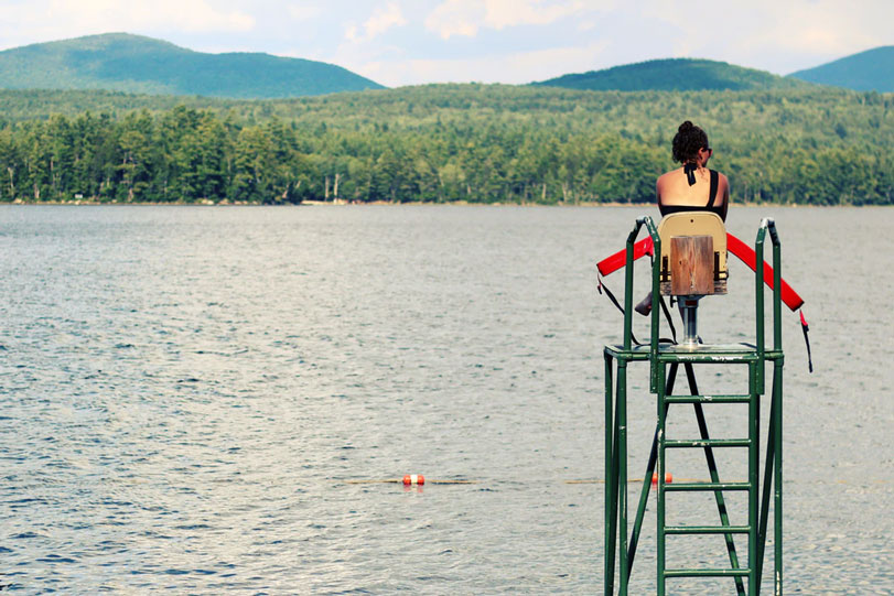 A lifeguard on her stand watching over swimmers