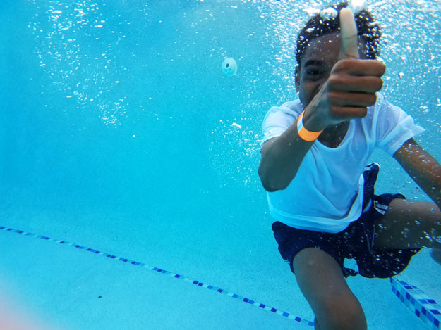 A boy submerged in a swimming pool giving a thumb's up
